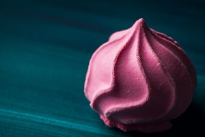 Pink pastel color meringue on dark green