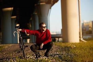Handsome guy in trendy shades sitting in squatting posture on grass, holding his fixed gear bicycle, relaxing after long ride. People, leisure, hobby, active healthy lifestyle and transportation