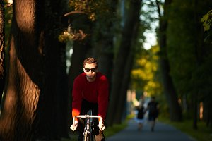 Candid shot of young hipster with bristle cycling along alley in public park. Trendy looking student enjoying ride on his fixed gear bike, commuting home from college. Hobby and active lifestyle