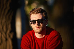 Close up portrait of handsome fashionable young bearded man wearing red sweater and trendy shades posing outdoors enjoying leisure time on weekend, walking in park, green trees in background