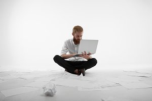 Finding for creative solution. Handsome unshaven office worker sitting on white floor, surrounded with paper sheets while working on laptop computer, looking at screen with concentrated expression