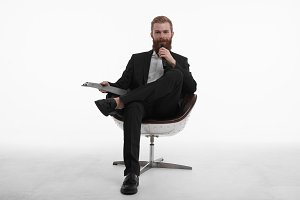 Live broadcasting. Portrait of confident young male professional news reporter with red beard sitting in chair in relaxed pose, holding clipboard and talking in microphone, dressed in stylish suit