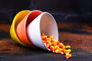 Traditional Halloween sweets - candy corn in bright colorful bowls