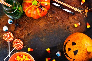 Halloween greeting card - drinks, candies and decor on dark background