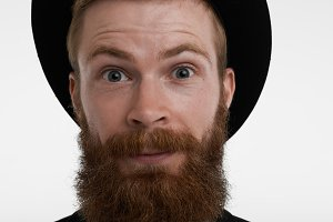 Close up highly-detailed portrait of astonished redhead bearded man in elegant hat raising eyebrows in surprise, amused with positive unexpected news. Human emotions, feelings, reaction and attitude