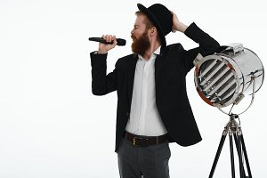 Cropped portrait of emotional handsome male with thick beard wearing hat, jeans and black jacket leaning elbow on spotlight lamp and singing a song in microphone during corporate party in karaoke bar