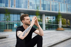 Urban lifestyle picture of fashionable young Caucasian man with beard and tattoo on arm sitting alone on stairs, clasping hands, having pensive sad look, making up mind after fight with his girlfriend