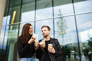 Dating, relationships and modern lifestyle concept. Happy young Caucasian male and female wearing stylish clothes standing against office building background, eating street food and drinking coffee
