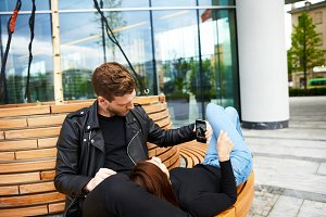 Beautiful Caucasian couple relaxing outdoors: attractive bearded young man sitting on bench and holding smart phone, showing pictures on social media to his girlfriend who is lying on his lap