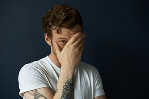 Masculinity concept. Headshot of handsome tattooed young European male fashion model dressed in white casual t-shirt looking out of his palm, flirting, having playful facial expression. Body language