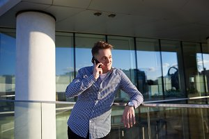 Handsome confident young man in shirt standing in urban surroundings, having nice phone conversation. Cheerful student or businessman talking on mobile outdoors. Technology and communication
