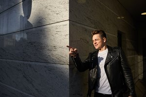 Urban portrait of trendy-looking young man wearing stylish leather jacket looking in front of him and pointing index finger after he came across a friend on street,having cheerful excited look