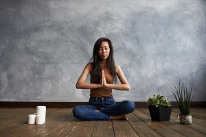 Beautiful barefooted Asian female practicing meditation with legs crossed and eyes shut, sitting on floor with candles and flowerpots, making namaste gesture, her face has calm and peaceful expression
