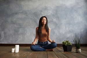 People, meditation and relaxation. Attractive brunette Korean girl wearing top and jeans sitting on wooden floor in half lotus pose, surrounded with candles and plant-pots, meditating with eyes closed