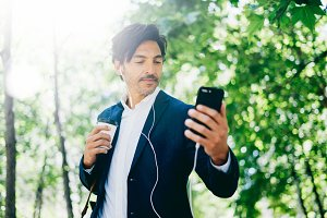 Handsome smiling businessman using smartphone for listining music while walking in city park.Young man making selfie portrait outdoor.Horizontal,blurred background.
