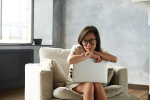 Pretty girl of Asian appearance in stylish eyeglasses relaxing on comfortable armchair in light spacious room with large window, holding generic laptop computer, looking away with dreamy expression