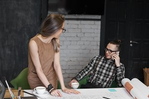 Two young colleagues working together in modern office interior. Beautiful female in dress studying plans and blueprints on desk while man in chair talking on cell phone, making business calls