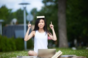 Lifestyle portrait of funny playful young woman of Asian appearance sitting on grass in park with book placed on her head, balancing it while doing homework using 4g internet on her generic laptop