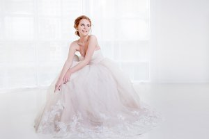 Portrait of a beautiful girl in a wedding dress. Sitting on the couch and laughs happily