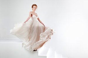 Portrait of a beautiful girl in a wedding dress. Bride in luxurious dress dancing and swinging hem skirt