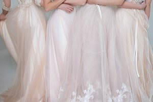 Four beautiful bridesmaid dresses in pastel colors are in each other's arms. Back, close-up lace skirts