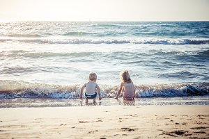 two kids play with wave on summer beach