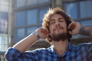 Bearded guy enjoying the music. Portrait of young handsome stylish man on the street.