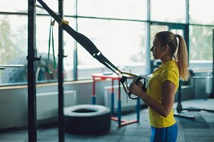 Young woman athlete trains using TRX, workout. Silhouette on background of interior