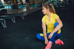 Girl in fitness club. Young female athlete sitting on floor and tied his shoelaces, ready to workout