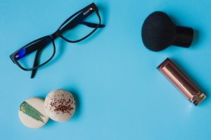 Still life with macaroons, glasses and lipstick, women's style, free space in center