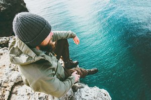Man traveler sitting on cliff alone