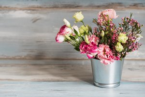 Spring flowers in small tin bucket. Bunch of different spring flowers in small tin bucket. Rustic wooden background. Free space left