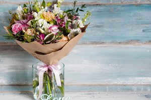 beautiful lush bouquet with different spring flowers, turquoise background, gift