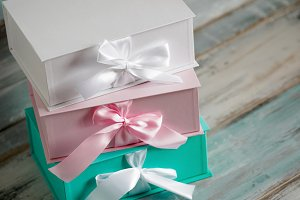 Three gift boxes, white, pink and turquoise. Top view diagonally on a wooden background. Gifts for your girlfriend