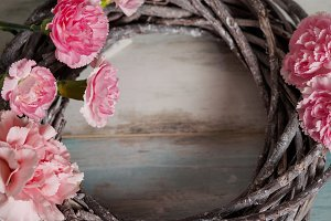 Round wreath of dry branches with pink flowers, frame on blue turquoise wooden background, place for text. Springtime and revival concept