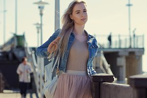 Young cheerful girl on the seashore. Young blonde woman smiling. Trendy style