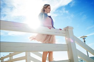 Young cheerful girl on the seashore leaning over on the wooden white fence. Young blonde woman smiling. Trendy beige skirt