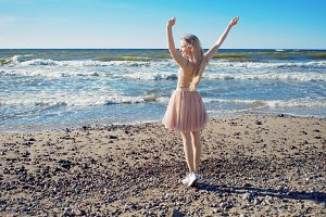 Young cheerful girl on the seashore. Young blonde woman smiling. Trendy beige skirt