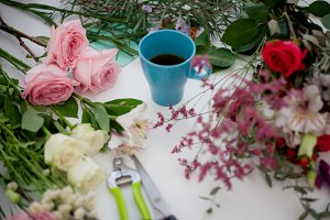 Cup of tea on the table, relax. Workshop florist, table with flowers, still life. Soft focus
