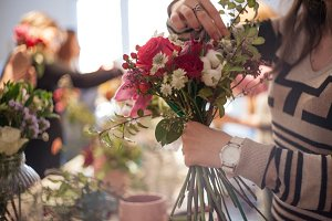 Workshop florist, making bouquets and flower arrangements. Woman collecting a bouquet. Soft focus