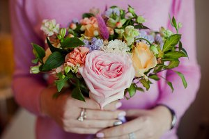 Girl in pink sweater holding a beautiful lush bouquet with roses, gift