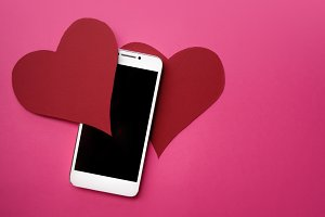 Hearts and smartphone. The concept to like in social networks or Dating app. pink background