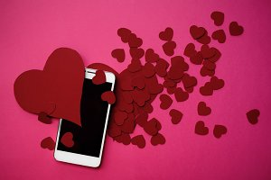 Many hearts and smartphone. The concept to like in social networks or Dating app. pink background