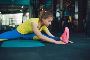 Girl in fitness club. Young woman in sportswear doing stretching, ready to workout
