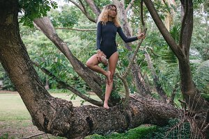 Attractive young woman in bikini posing on tropical tree trunk in forest