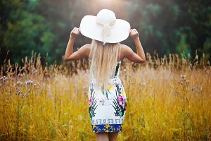 Beauty women Outdoors enjoying nature. Girl in a straw hat, back