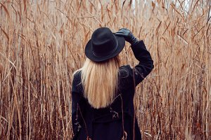 Portrait of young attractive woman in black coat and hat. Autumn landscape, dry grass. Look back. Holding the hat hand