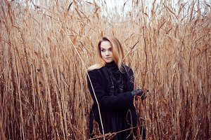 Portrait of young attractive woman in black coat and hat. Autumn landscape, dry grass