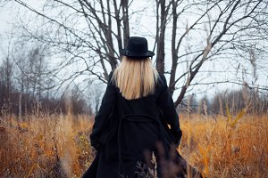 Portrait of young attractive woman in black coat and hat. She goes through the field. Autumn landscape, dry grass. Look back