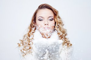 Woman Blowing Snow, girl in  warm knitted scarf and gloves, portrait on  white background, close up